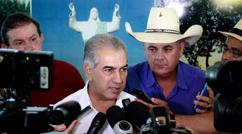 O governador Reinaldo Azambuja, durante entrevista nesta sexta-feira em Três Lagoas, observado pelo prefeito Angelo Guerreiro, de chapéu, logo atrás (Foto: Chico Ribeiro)
