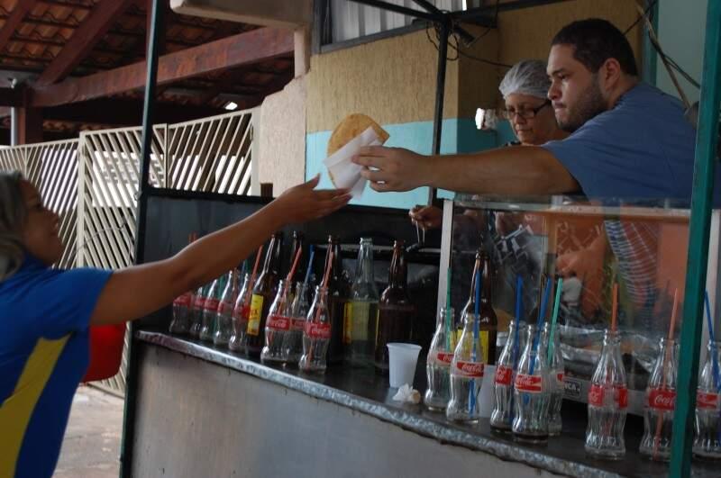 Renato atende a clientela enquanto a mãe frita os pasteis e seu Irineu monta. (Foto Pedro Peralta)