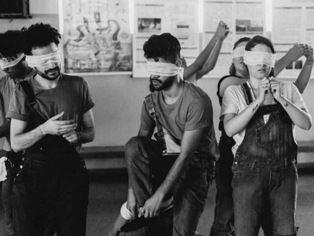 Com os olhos vendados, o grupo se movimenta e encena no palco (Foto: Divulgação)