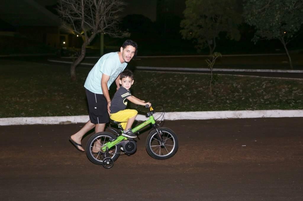 Daniel Silva ajudando o filho andar de bicicleta (Foto: Kisie Ainoã)