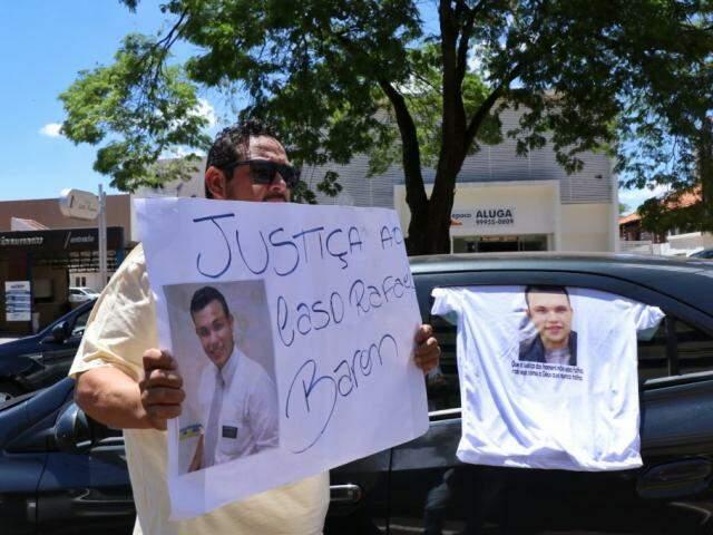 Motorista de aplicativo segura cartaz durante protesto nesta manhã em Campo Grande, cobrando a prisão do assassino de Rafael Baron. (Foto: Henrique Kawaminami)