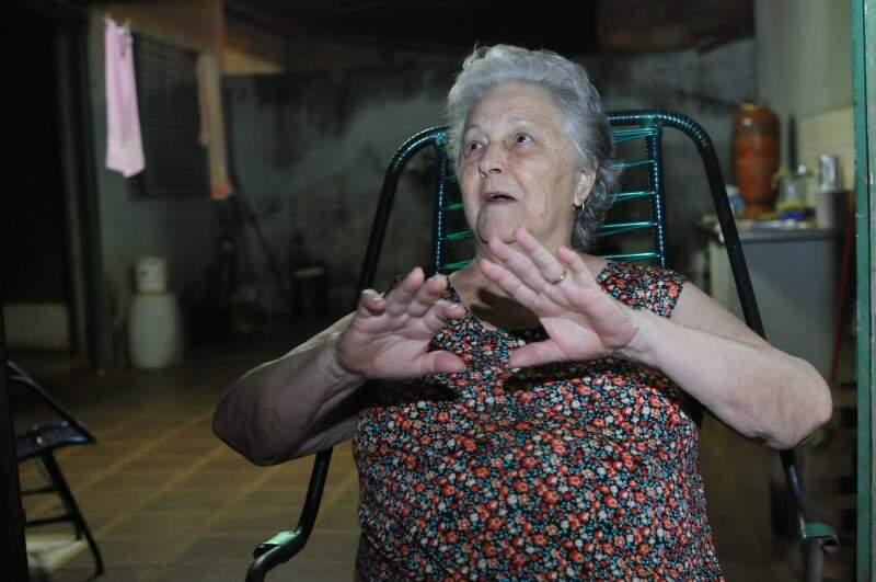 A senhora Pedrosa apela para a tolha molhada para vencer o calor. (Foto: Alcides Neto)