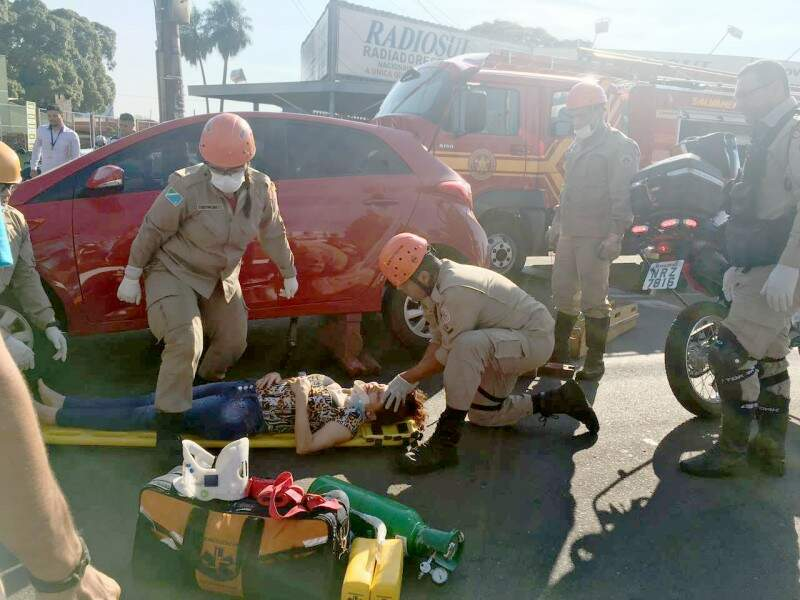 Mulher sendo socorrida após ser retirada debaixo do carro (Foto: Direto das Ruas)