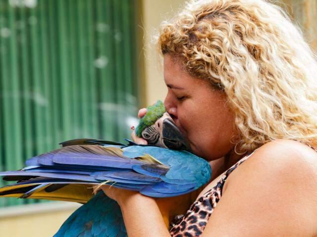 A servidora Sandra Gomes e a arara Jade. (Foto: Kisie Aimoã)