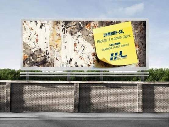 """A peça trazia um outdoor com as folhas descoladas e um """"post it"""" gigante alertando sobre a importância da reciclagem de papel."""