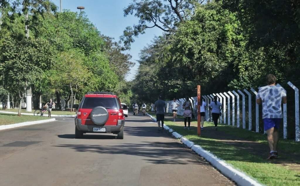 Veículo trafegando no Parque dos Poderes ao lado de corredores nesta manhã (Foto: Fernando Antunes)