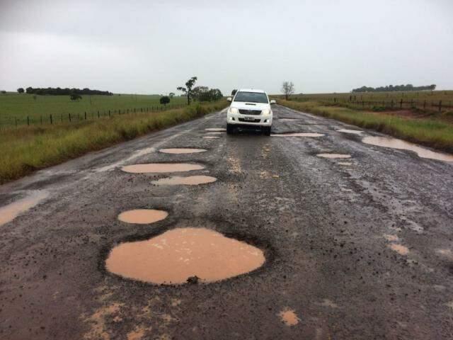 Caminhonete tentando passar sem cair nos buracos na rodovia (Foto: Direto das Ruas)