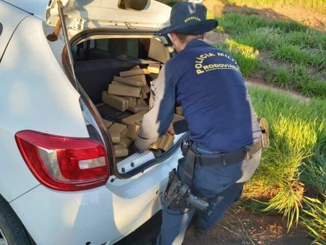 Policial contando os tabletes de maconha encontrados no veículo. (Foto: Divulgação/PMR)
