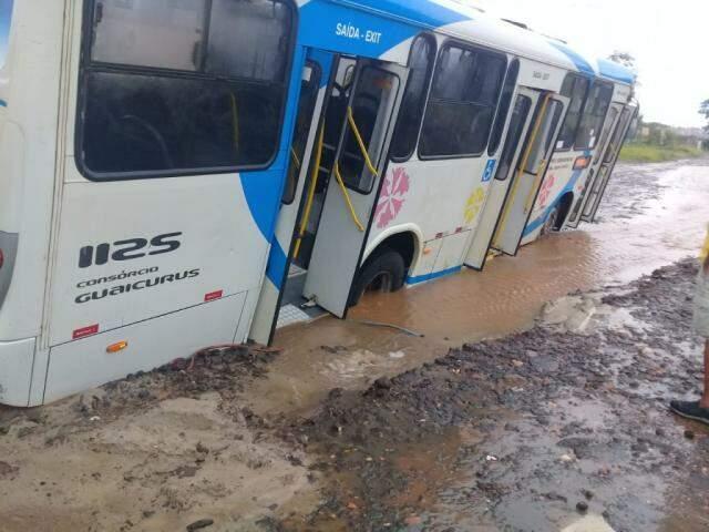 Ônibus ficou com todas as rodas atoladas e quase tombou por conta de rua alagada (Foto: Direto das Ruas)