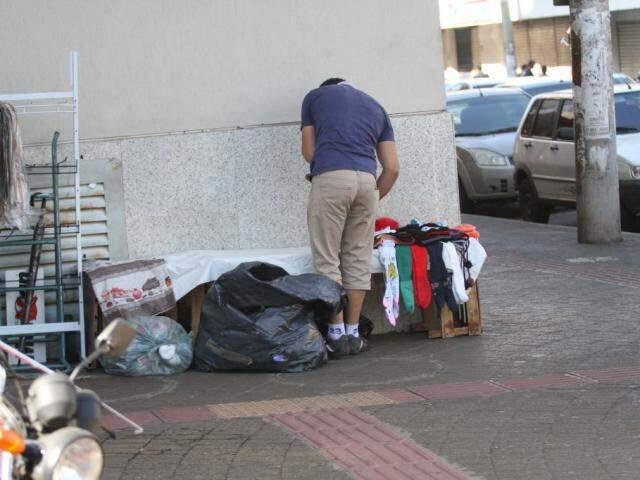"""Vendedor ambulante montando sua """"banca"""" na esquina da Barão com a 14 de Julho (Foto: Saul Schramm)"""