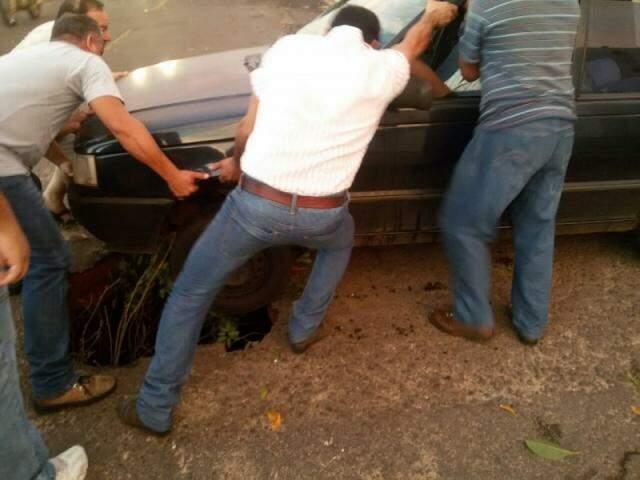 Populares ajudam a retirar veículo que ficou com a roda dentro de cratera (Fotos: Direto das Ruas)