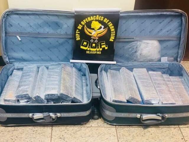 Droga estava em duas malas no compartimento de bagagens e, através do bilhete de passagem a mulher foi identificada. (Foto: DOF/Divulgação)