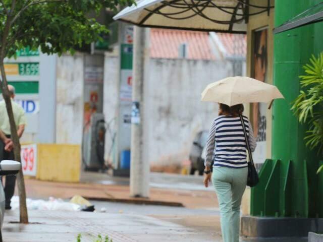 Mulher prevenida com guarda-chuva andando por rua de Campo Grande hoje (Foto: André Bittar)