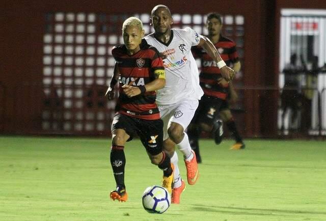 Neílton, ex-Santos e Botafogo, carrega a bola e é perseguido pelo lateral do Corumbaense, Valdinei (Foto: Tiago Caldas / E.C. Vitória / Divulgação)