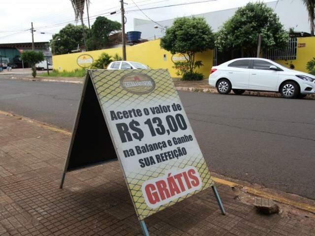 """Placa do outro lado da rua lança o desafio """"quem acertar R$ 13 na balança come de graça"""" (Foto: Saul Schramm)"""