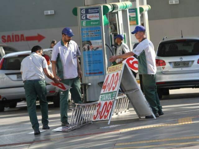 Funcionários de posto trocam placas que apontam o preço do produto em Campo Grande (Foto: Saul Schramm)