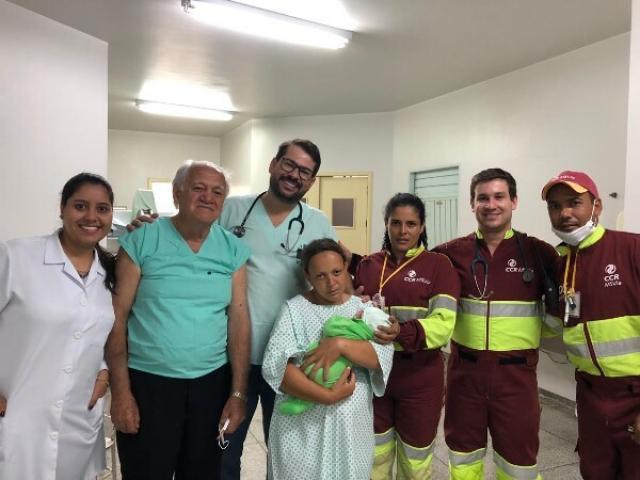 Mãe com bebê no colo e ao lado da equipe da CCR MSVia que realizou parto e de funcionários de hospital (Foto: Divulgação/CCR MSVia)