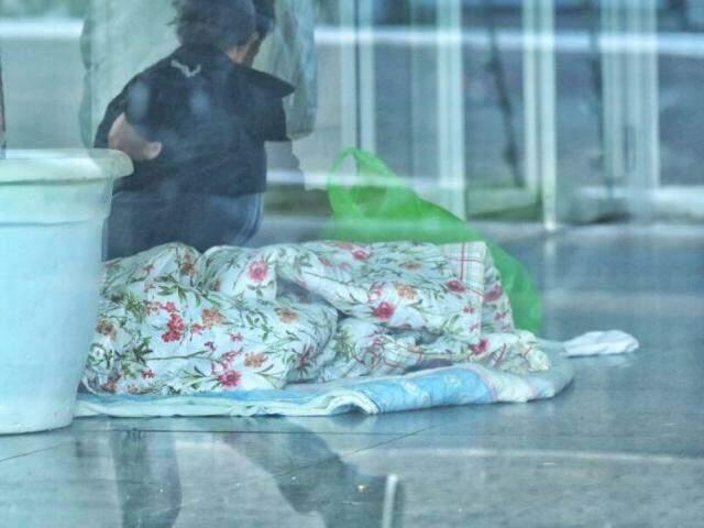 Mulher dormindo dentro de agência bancária no Centro de Campo Grande. (Foto: André Bittar)