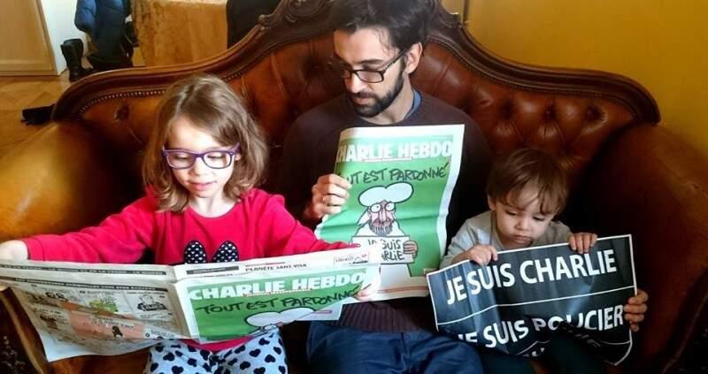 Julia, o pai André Mazini e o irmãozinho lendo Charlie Hebdo.
