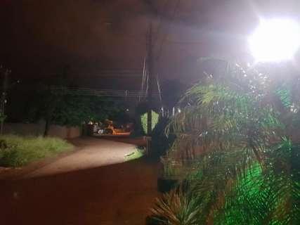 Sem iluminação, moradores do bairro Parque Dallas instalam refletor em rua