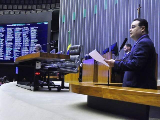 Deputado federal Fábio Trad (PSD/MS), na tribuna, à direita, na Câmara dos Deputados lendo relatório sobre projeto.(Foto: Divulgação/Assessoria).