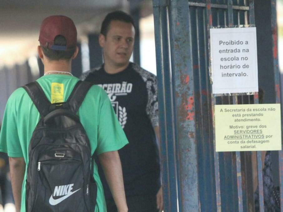 Alunos sendo recebidos na Escola Estadual Joaquim Murtinho, onde aviso sobre greve foi afixado no portão (Foto: Saul Schramm)