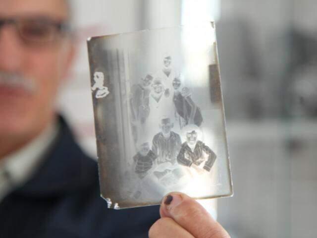 Nilson mostra um negativo de vidro, da sua coleção de câmeras e objetos antigos. (Foto: João Paulo Gonçalves)