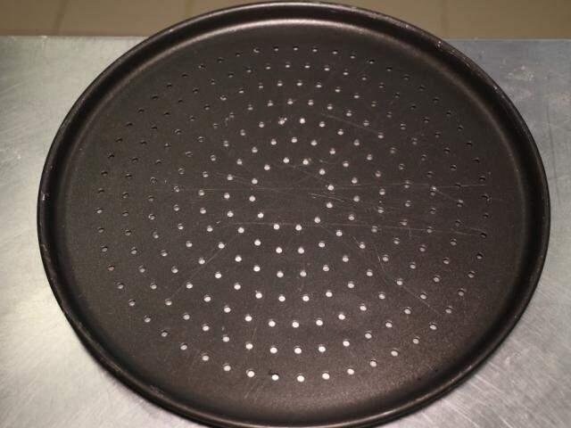 Use uma assadeira redonda com furinhos para assar a massa da pizza (Foto: Paulo Francis)