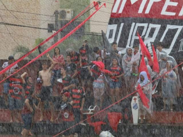Torcida embaixo de chuva na arquibancada do estádio Ninho da Águia (Foto: Franz Mendes)