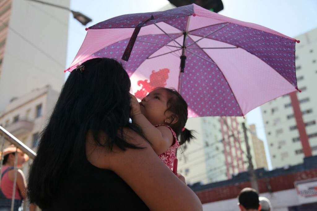 Mulher e sua filha assistindo ao desfile de aniversário da cidade protegidas com uma sombrinha (Foto: João Paulo Gonçalves)