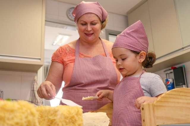 Com ajudante de 2 anos, avó reveza expediente entre cuidar da neta e fazer torta
