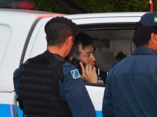 Policial rodoviário federal fala ao telefone dentro de viatura da PM depois de atira e matar empresário (Foto: Simão Nogueira)