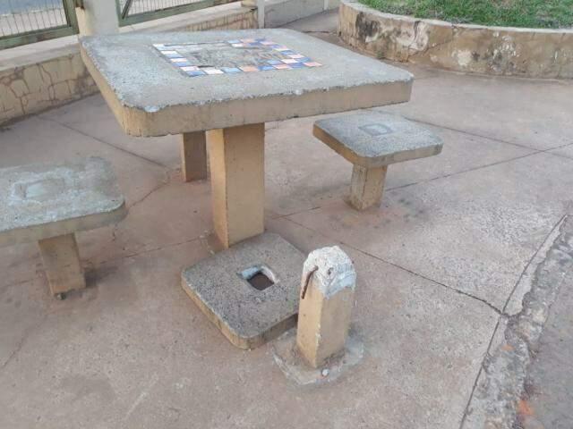 Um dos bancos da mesa de concreto está no chão no Elias Gadia. (Foto: Direto das Ruas).