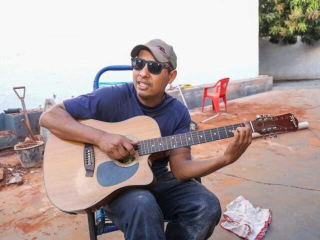 Na pausa da obra, Leandro Àvila pega o violão e solta a voz (Foto: Paulo Francis)
