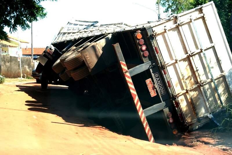 Carreta caiu ao passar pela rua de chão onde há uma valeta de aproximadamente meio metro de profundidade aberta pela enxurrada do temporal que caiu no domingo. (Foto: Umberto-Zum).