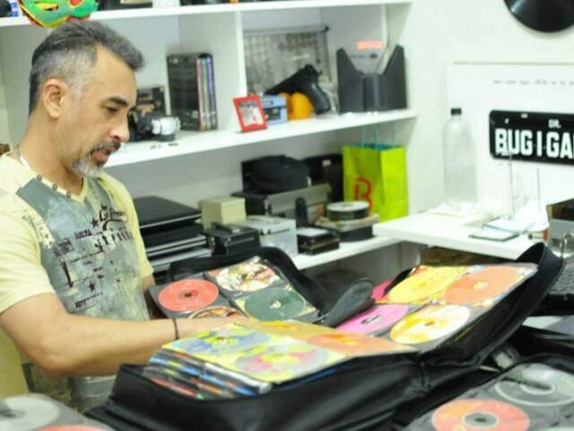 Geraldo e a coleção, que está divida em 5 álbuns. (Foto: Alcides Neto)
