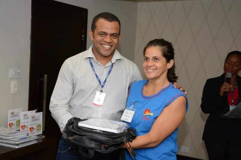 Selecionada em oficina recebe do gerente de RH do JBS, Rubens Bernardes, material para a oficina. (Foto: Divulgação)