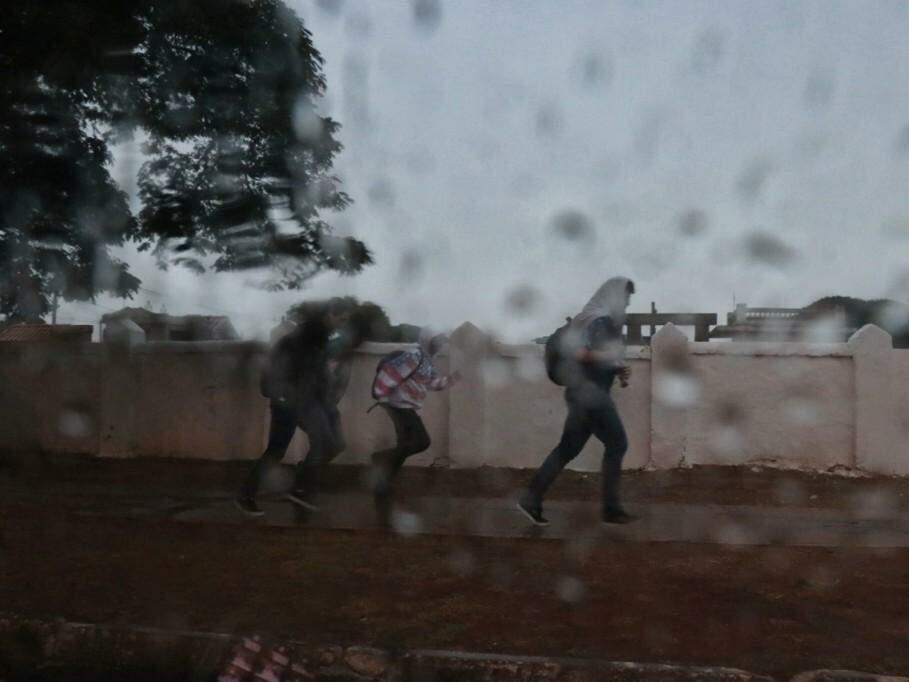 Na decida do ônibus, passageiros correm para não pegar chuva, em Campo Grande (Foto: Henrique Kawaminami)
