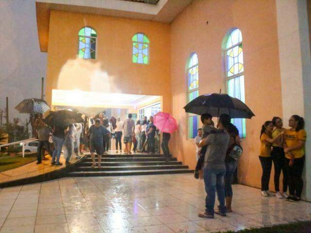 Féis se protegendo da chuva durante apresentação na Capela São Pedro e São Paulo (Foto: Paulo Francis)