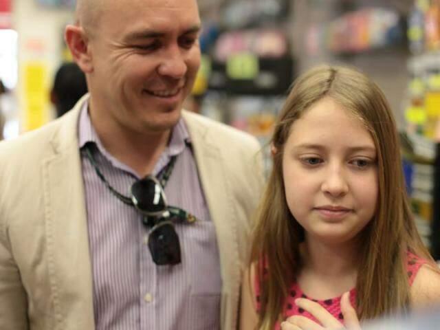 Pai abraçando filha em loja de papelaria do Centro (Foto Fernando Antunes)