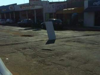 Placa colocada por moradores para sinalizar o buraco da Av Bandeirantes (Foto: Direto das ruas)