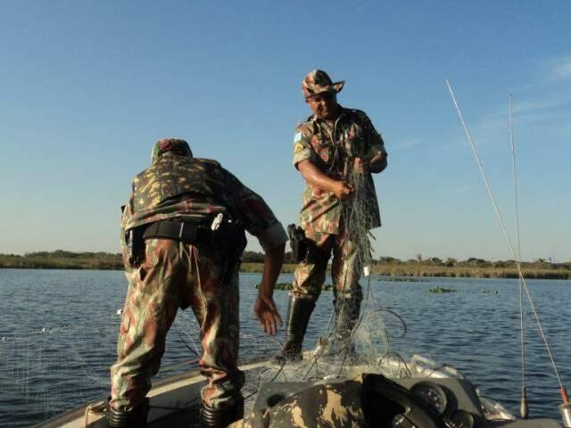 Policiais militares ambientais apreendendo rede de pesca em rio de MS (Foto: Divulgação/ PMA)