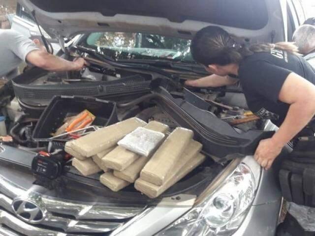 Policiais fazendo a retirada da droga do compartimento oculto do carro. (Foto: AgoraMS)