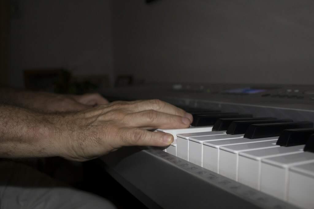 Na sala de casa, Miguelito transforma a inspiração em música que fluí pela ponta dos dedos