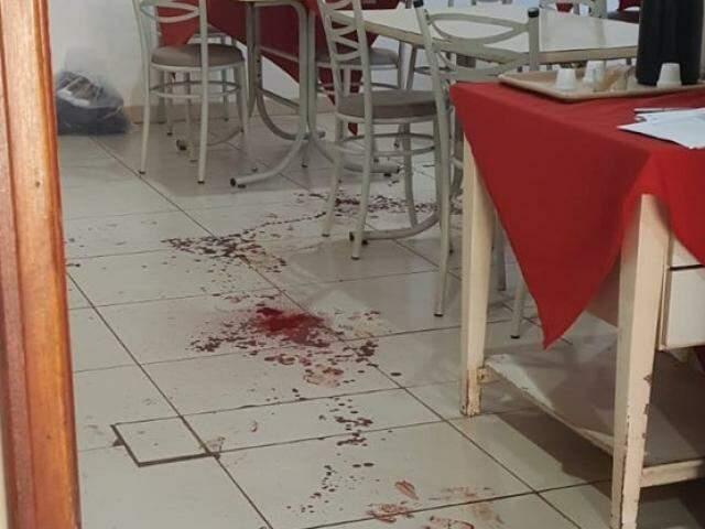 Marcas de sangue ficaram pelo chão de restaurante, após dono ser atingido por quatro tiros (Foto: Fábio Campos/Rádio Caçula)