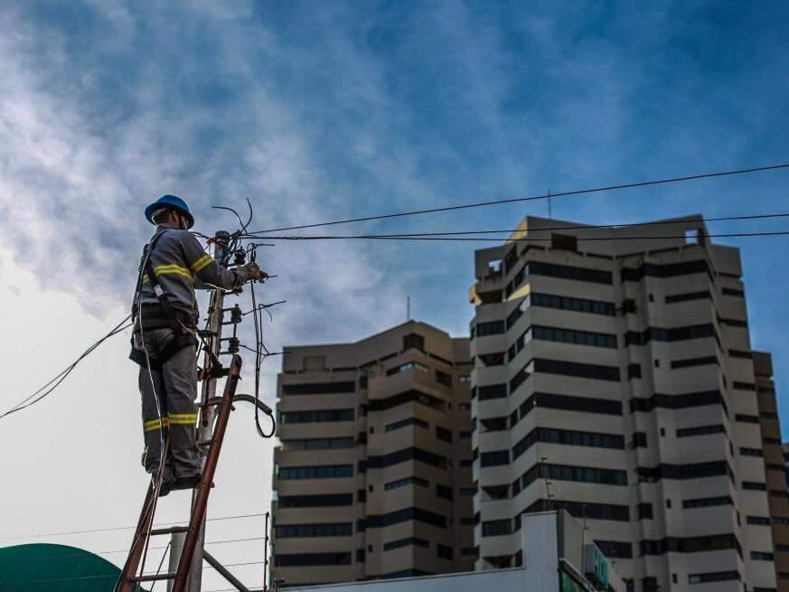 Técnico prestador de serviço da Energisa realiza a reposição de fios que foram furtados no centro de Campo Grande, no dia 11. (Foto: Fernando Antunes)