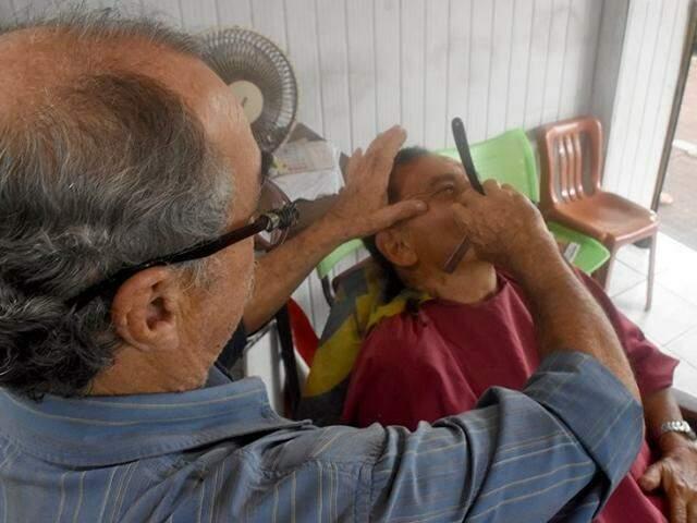 Habilidoso com a navalha, Toninho faz a barba dos clientes e finaliza o corte com o mesmo instrumento. (Foto: Roberto Higa)
