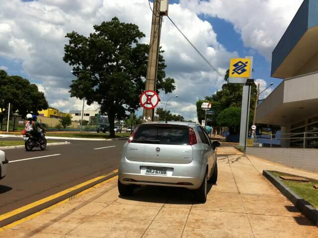 Leitor flagrou carro estacionado na calçada mesmo com placa de proibição.
