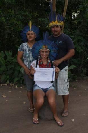 Ao lado dos pais na aldeia Limão Verde, segurando o diploma. (Foto: Dionedison Terena)