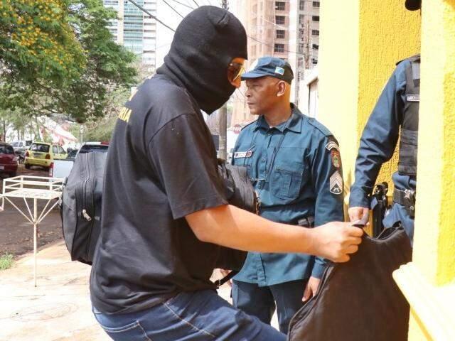 Policiais da Corregedoria com rostos cobertos com touca chegando com objetos apreendidos (Foto: Henrique Kawaminami)